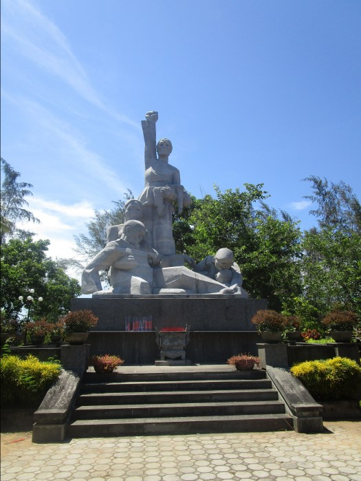 Historical Places to visit in Vietnam: My Lai Memorial. The memorial statue shows a mother and her dying family surrounding her as she defiantly