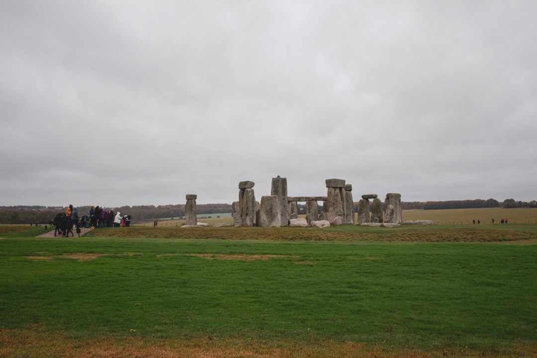 Crowds walking around Stonehenge on a cloudy day