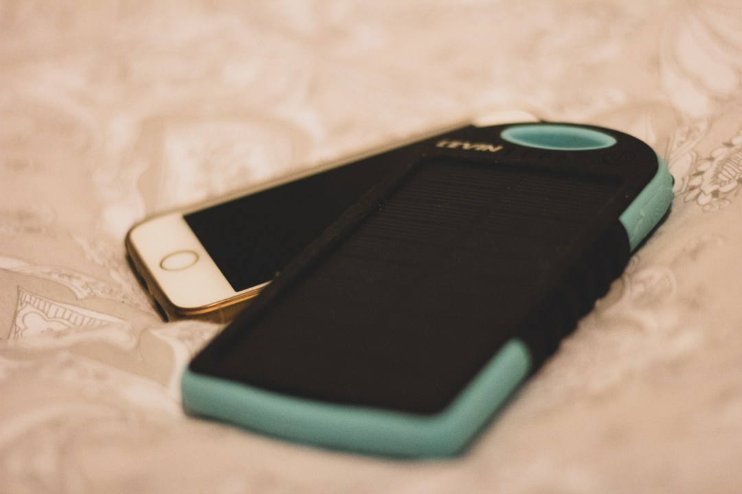 Close up of blue solar charger and iphone
