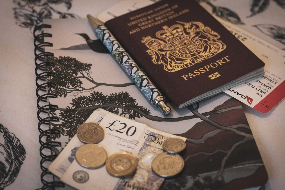 Cash and passport sit on top of a notebook with a pen