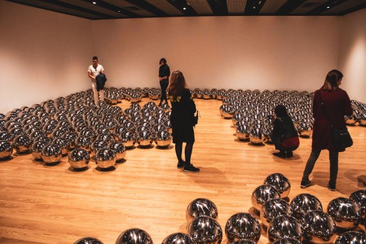 People standing amongst silver balls on the floor of art gallery