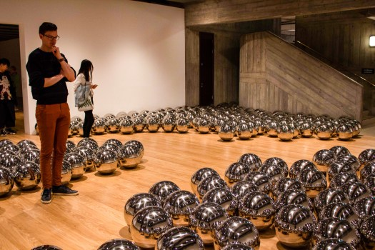 Man stands observing silver balls on the floor of art gallery