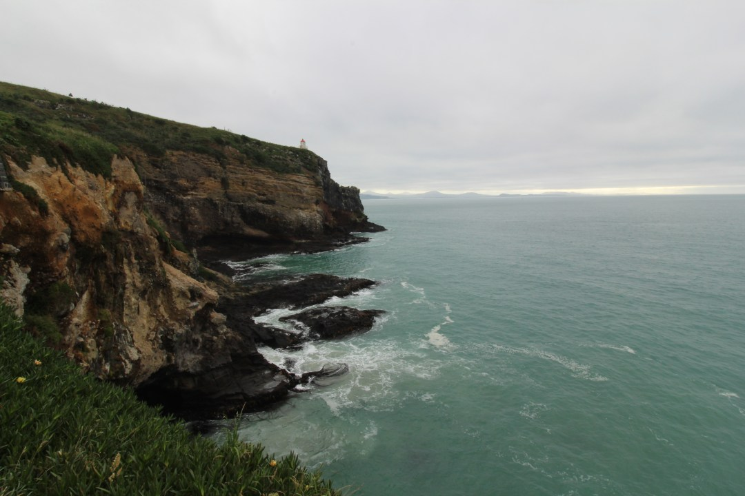 Views over the otago peninsula coastline on a cloudly day with waves hitting the rocks