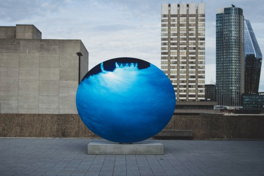 Blue sphere reflecting the sky sits atop a gallery rooftop