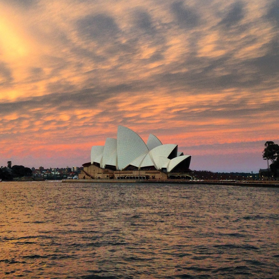 Yellow, pink, and purple clouds of a sunset over Sydney Opera House and the harbour