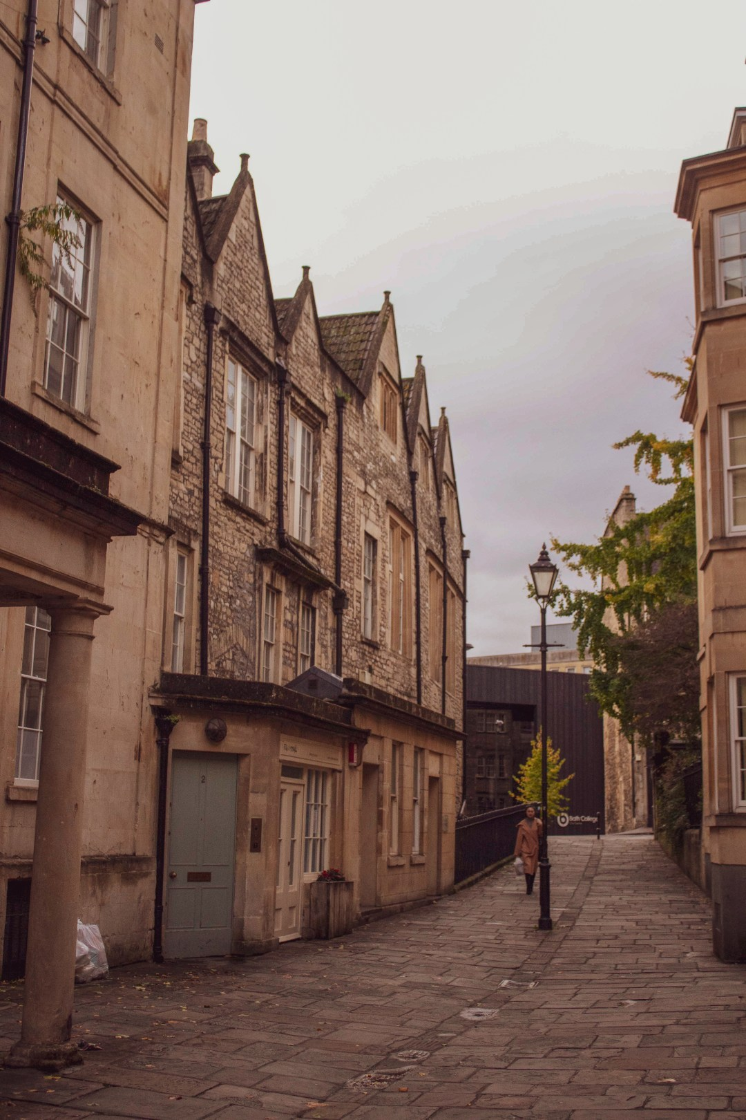 Quiet street of Bath with quaint stone houses and an old street lamp