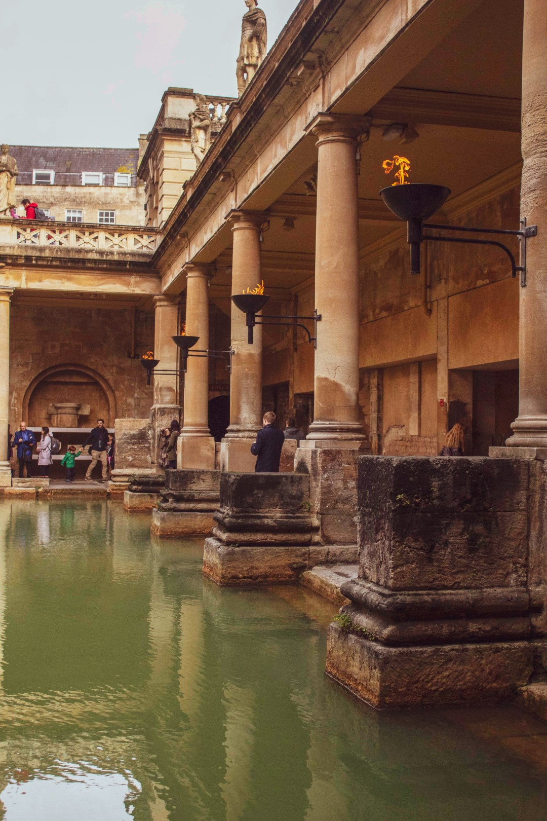 Beacons with fire sit along stone pillar surrounded green Roman Bath waters