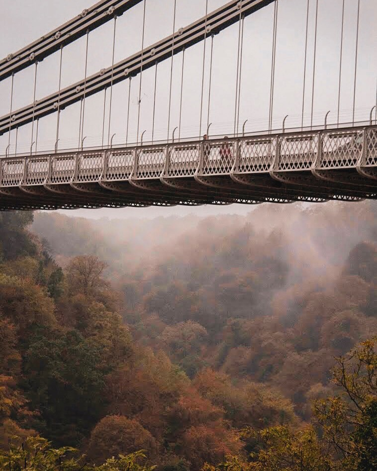 Visit Bristol In One Day Trip - Explore Bristol's harbourside, famous landmarks, and beautiful countryside for an immersive taste of history, world exploration, and engineering! Misty clouds beneath Clifton Suspension Bridge add a moody vibe to your trip.