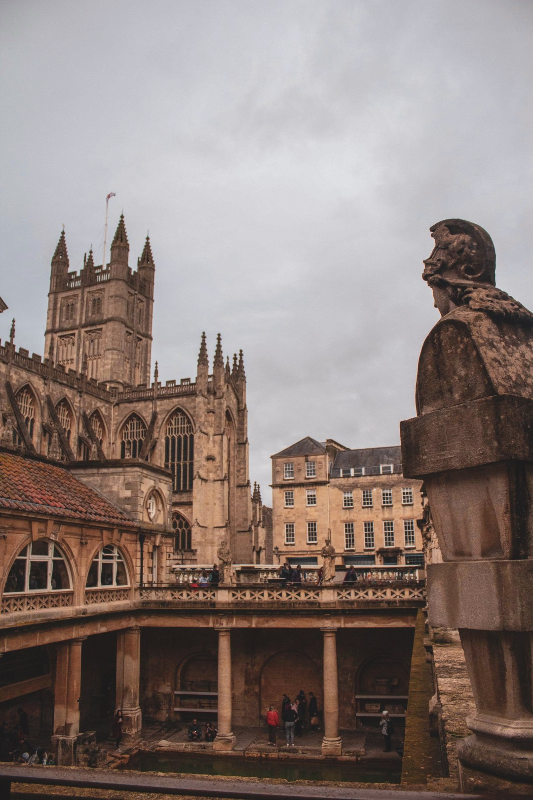 Roman Emperor statue looks over Roman Baths and Bath Abbey with a cloudy sky