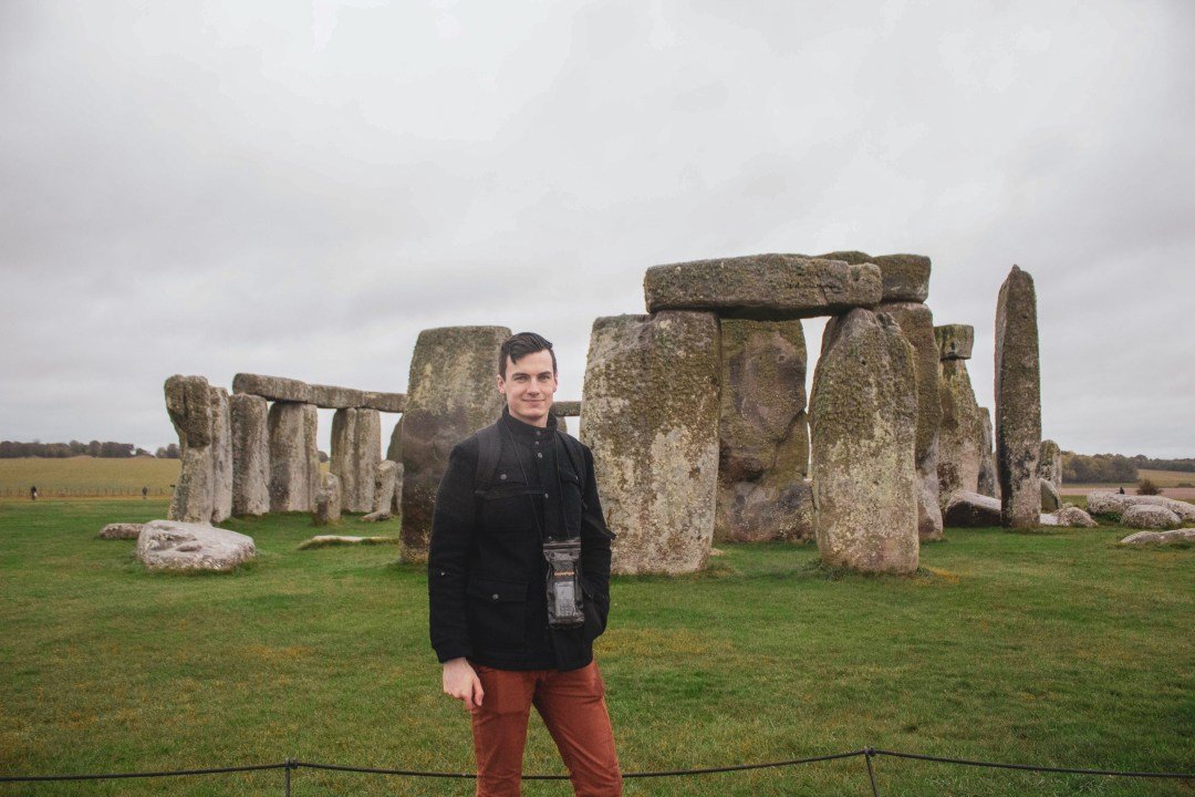 Man smiles in front of Stonehenge in the rain