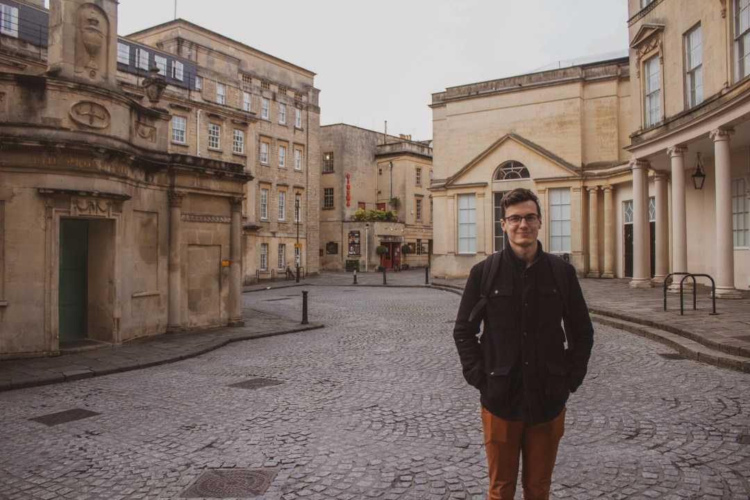 Man smiles at the camera in an empty street in Bath