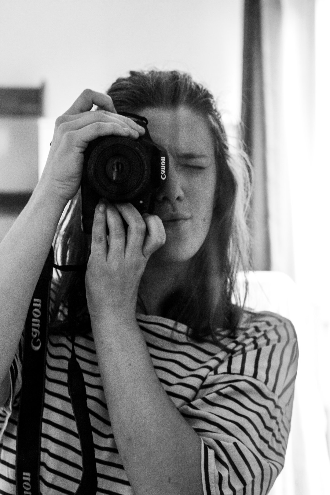 black and white self portrait of girl taking photo in mirrror
