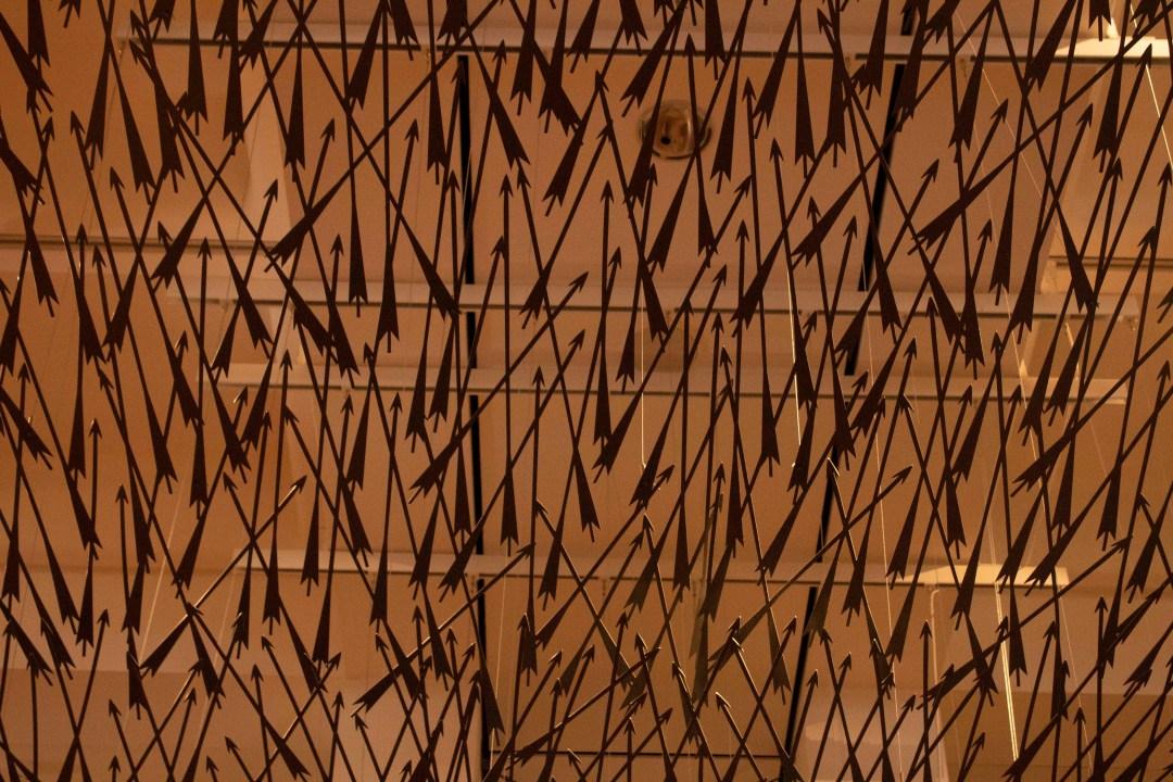 Metal arrows create art display at the ceiling