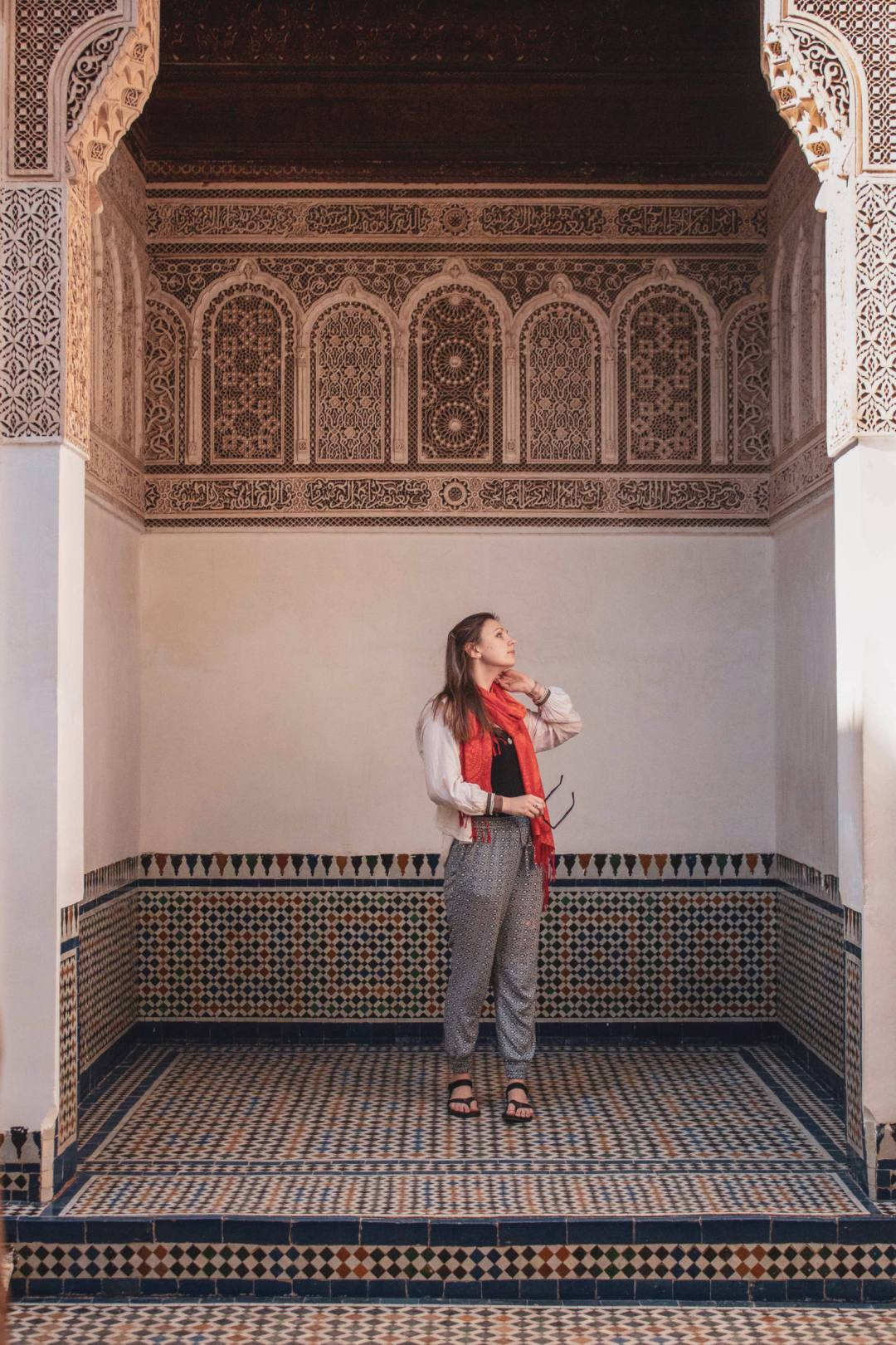 woman looks up in archway of Bahia Palace Marrakech