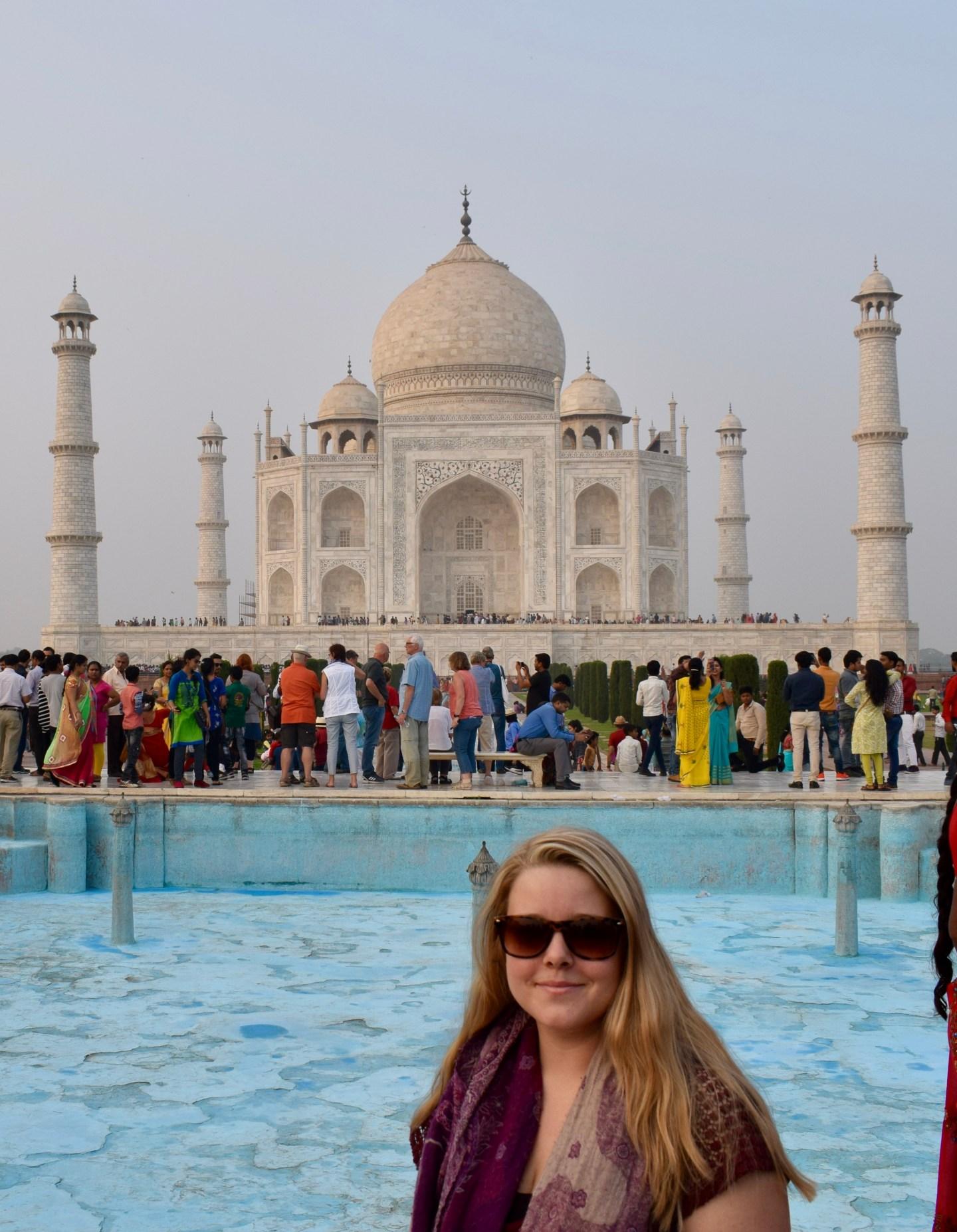 girl smiles in front of taj mahal in india