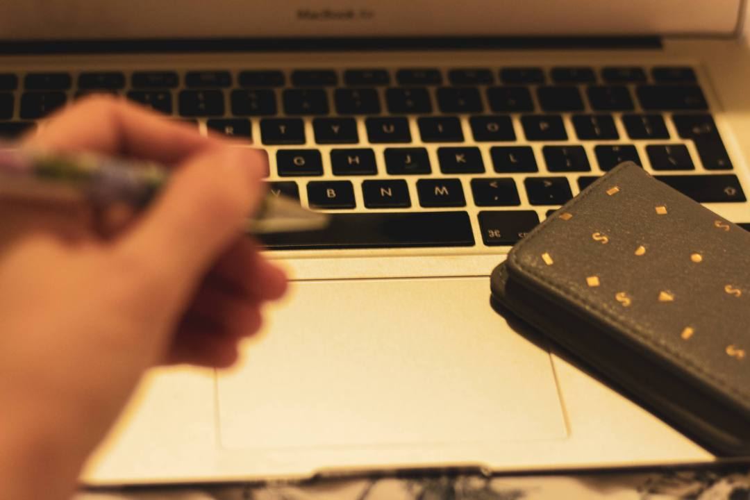 Wallet on laptop keyword with hand holding pen