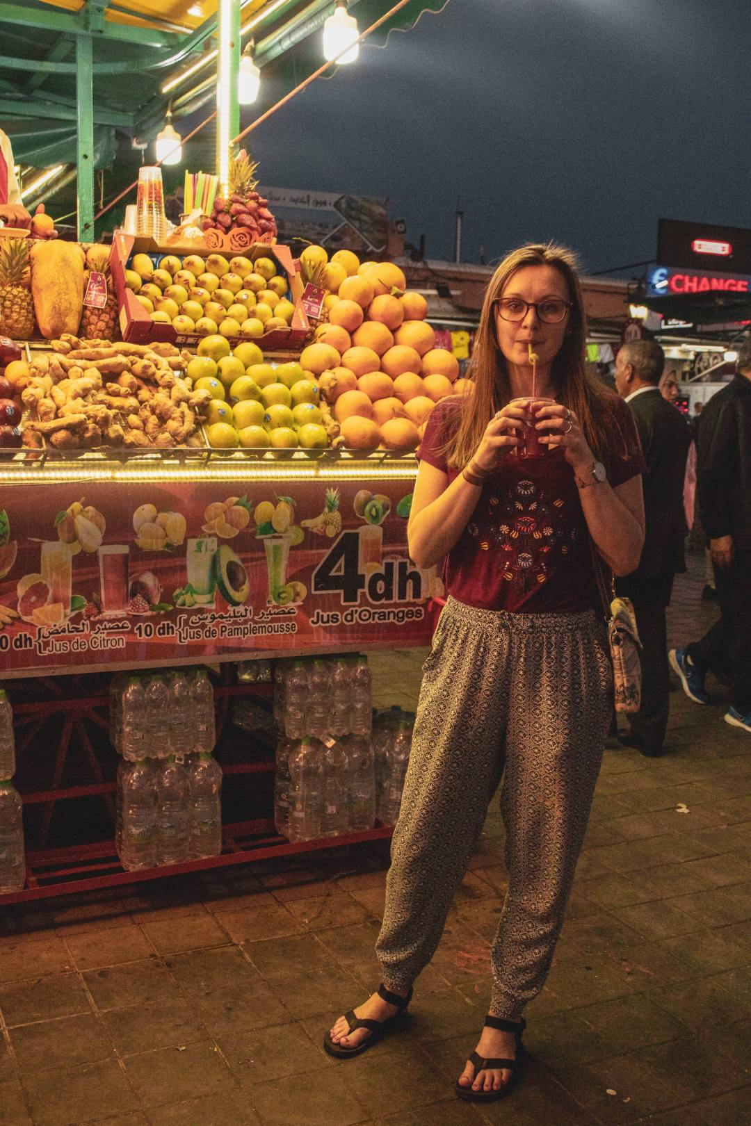 woman sips a smoothie in front of a fruit stall in Marrakech
