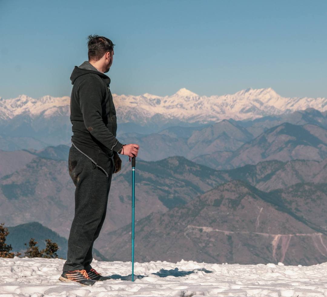 man stands with trekking poles overlooking snowy mountains