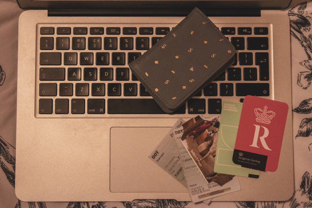 tickets and purse on laptop keyboard
