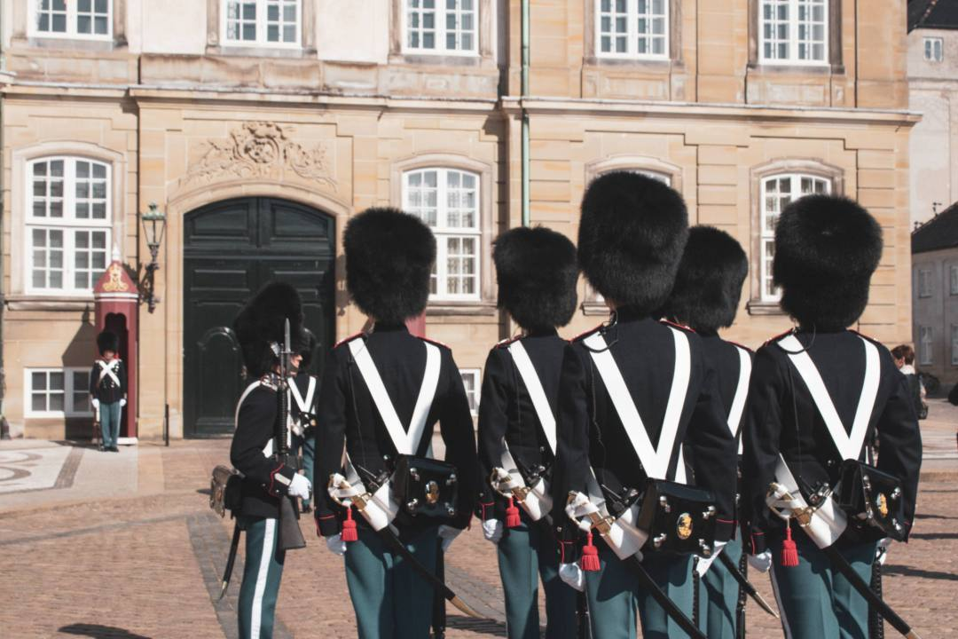 guards standing to attention dressed in uniform outside Copenhagen palace