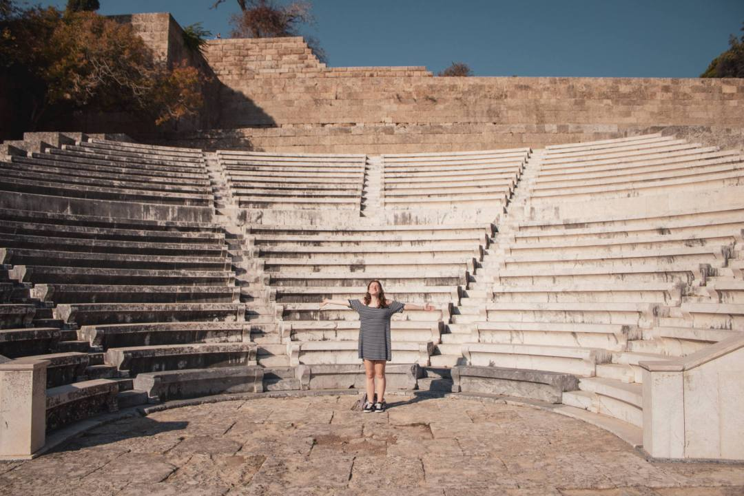 Woman standing in middle of Greek amphitheatre ruins