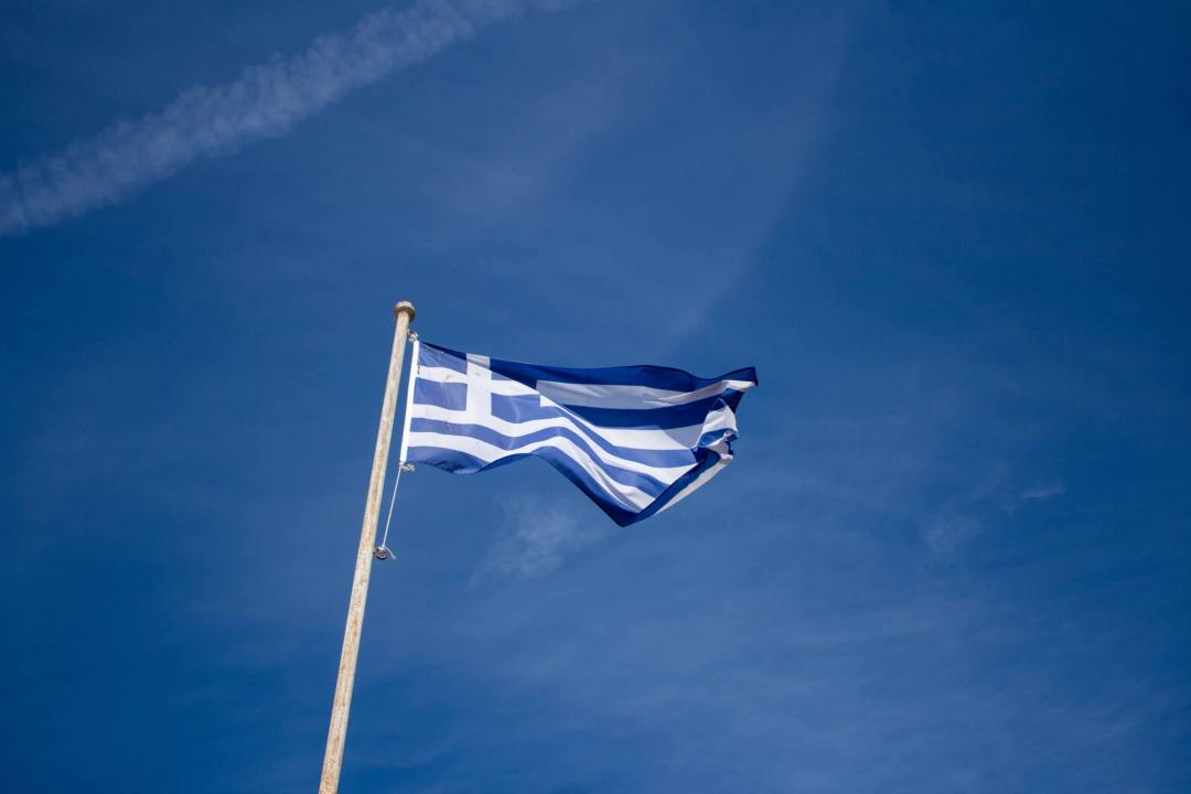 Greek flag blows in blue skies