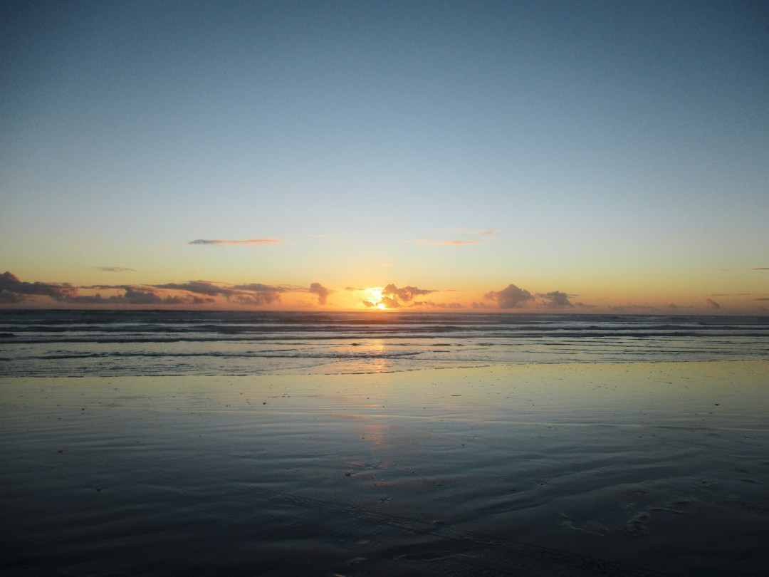 still waters on beach at sunset in New Zealand