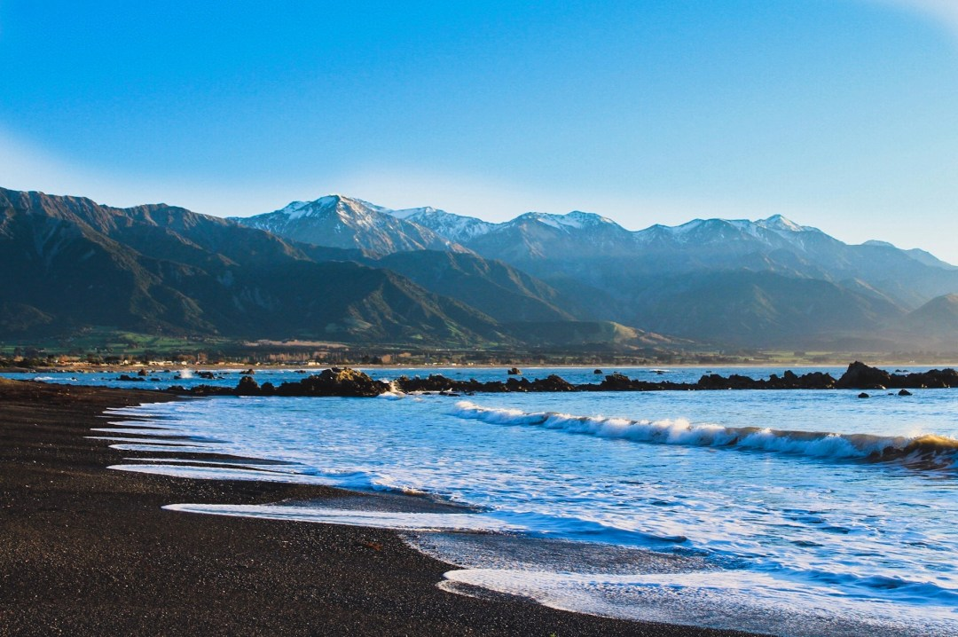 kaikoura beach at sunrise with gentle waves in front of mountains