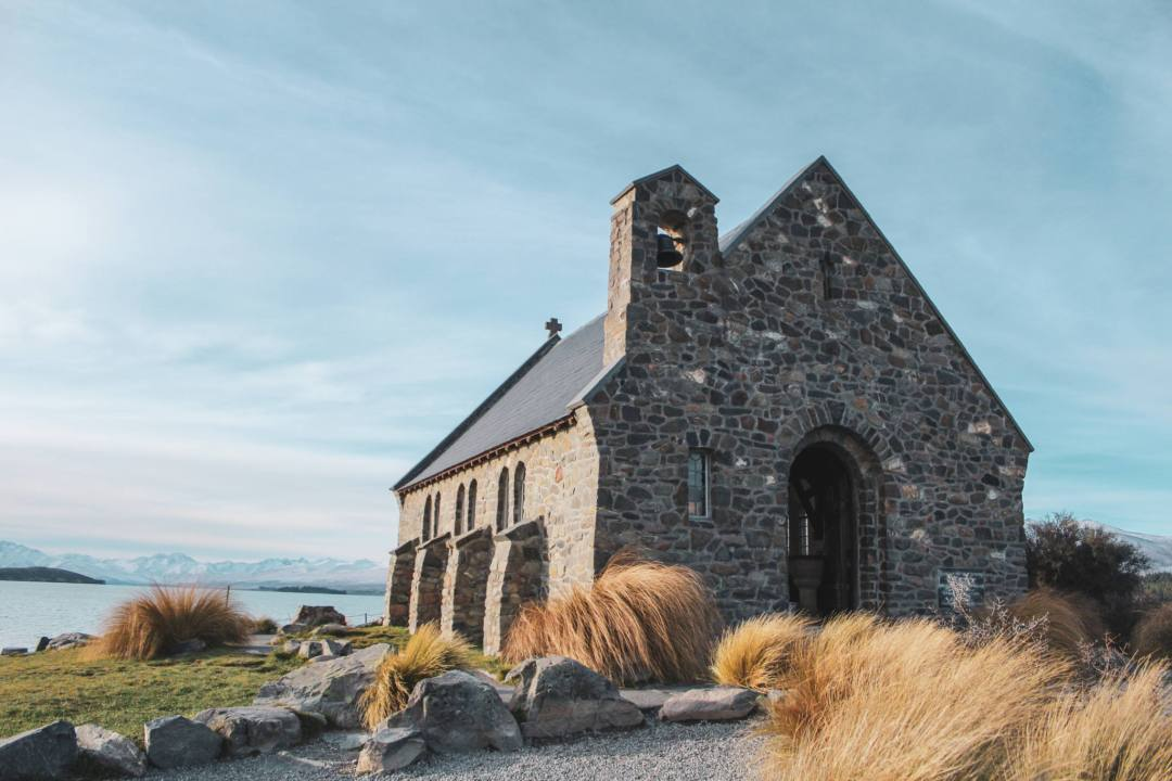 small church building in front of lake with mountains in distance