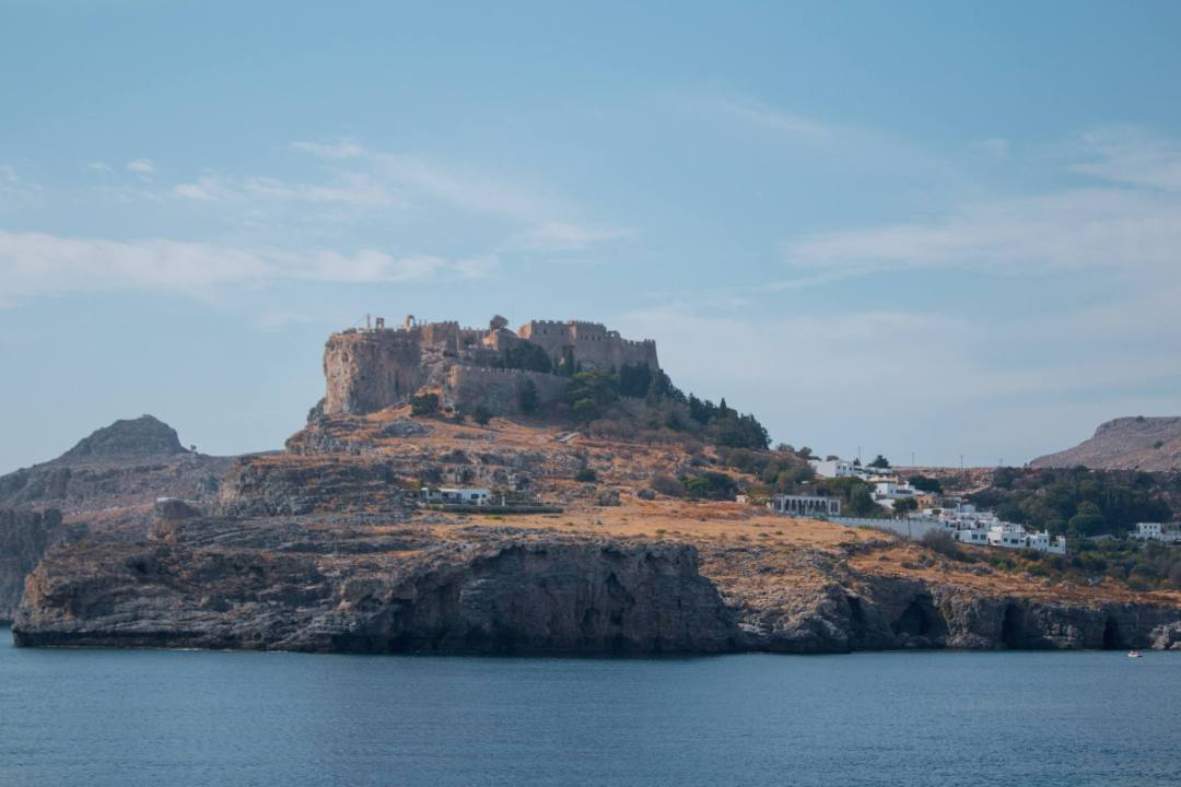 View of lindos acropolis standing on cliff edge in sunlight