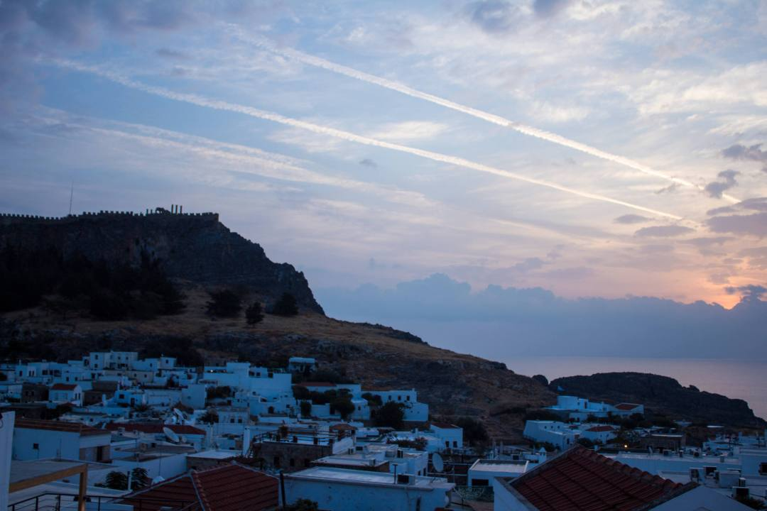 sun rises over lindos acropolis and village with cloudy sky