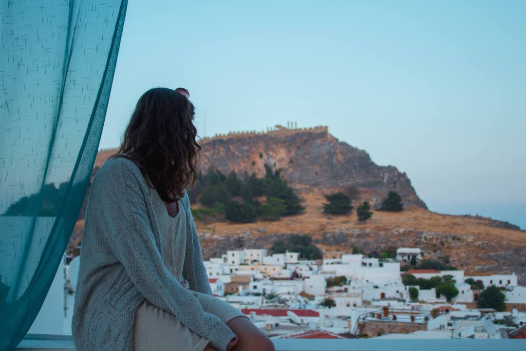 Woman sits on balcony overlooking Lindos village and acropolis at sunset