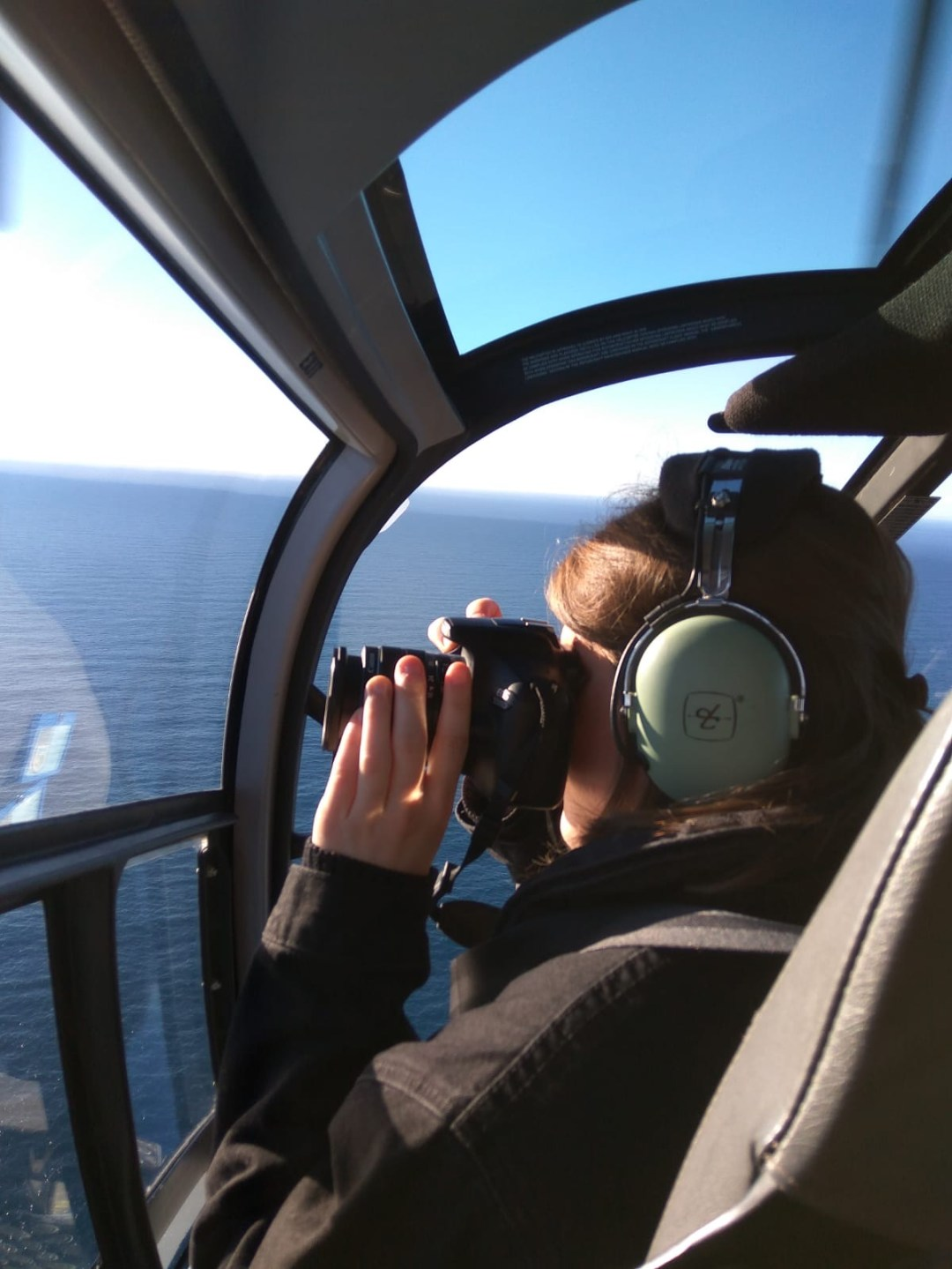 woman takes photo in helicopter