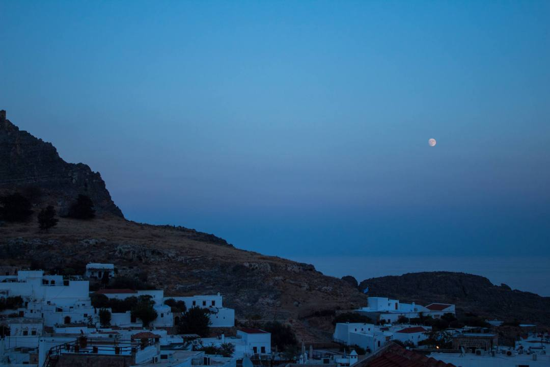 moon rises over lindos village at sunset