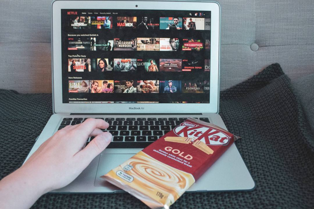 laptop with netflix on screen and chocolate resting on laptop with hand on keyboard
