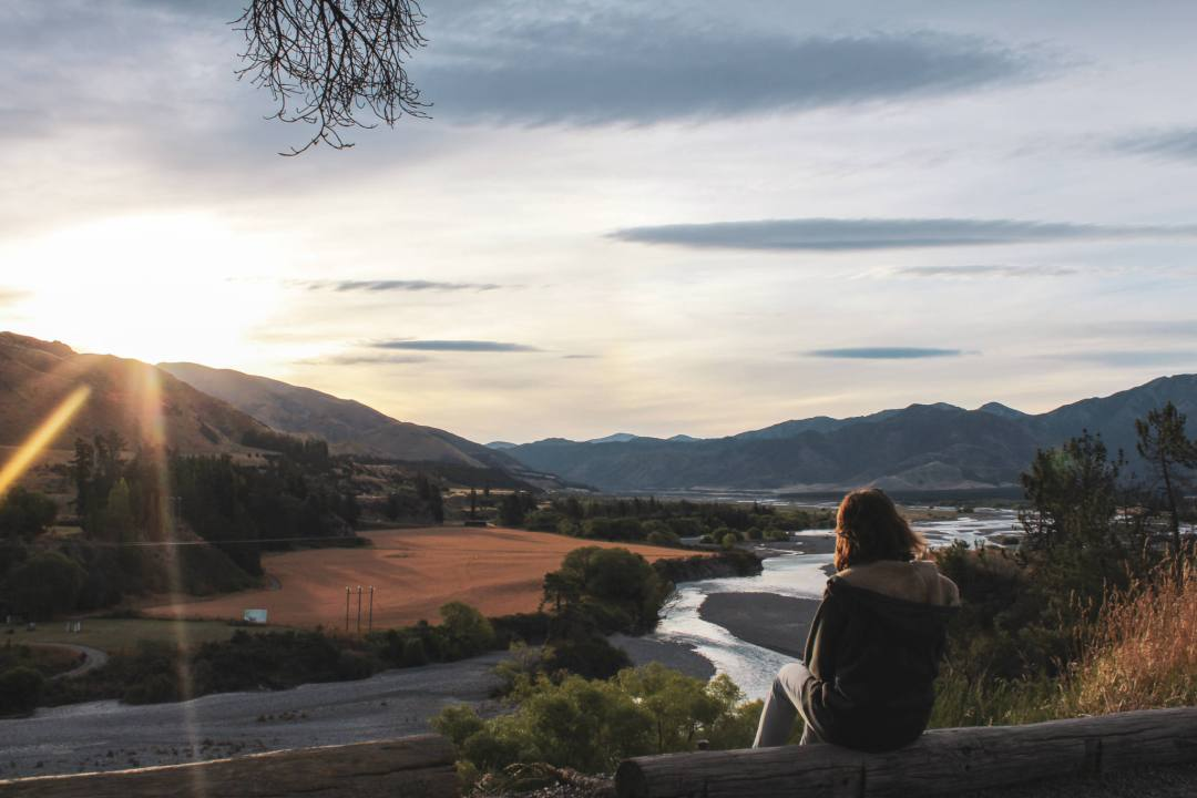 Traveller watching sunset over river and mountains