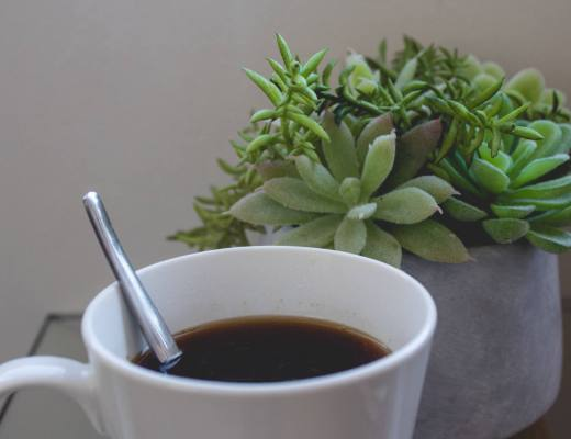 coffee in white mug next to plant