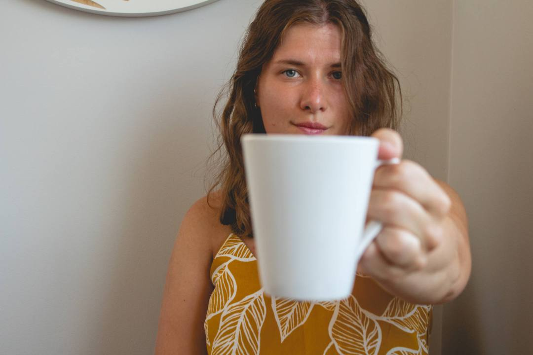 woman holds out white mug