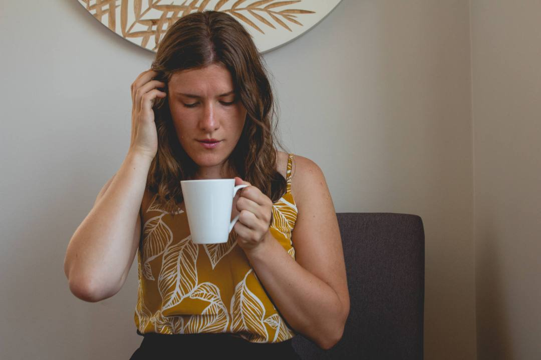 woman looks at mug in coffee shop
