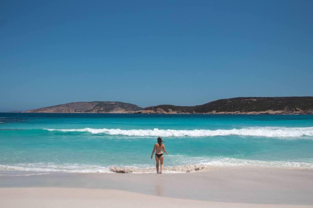 Woman walking into ocean at beach in Esperance