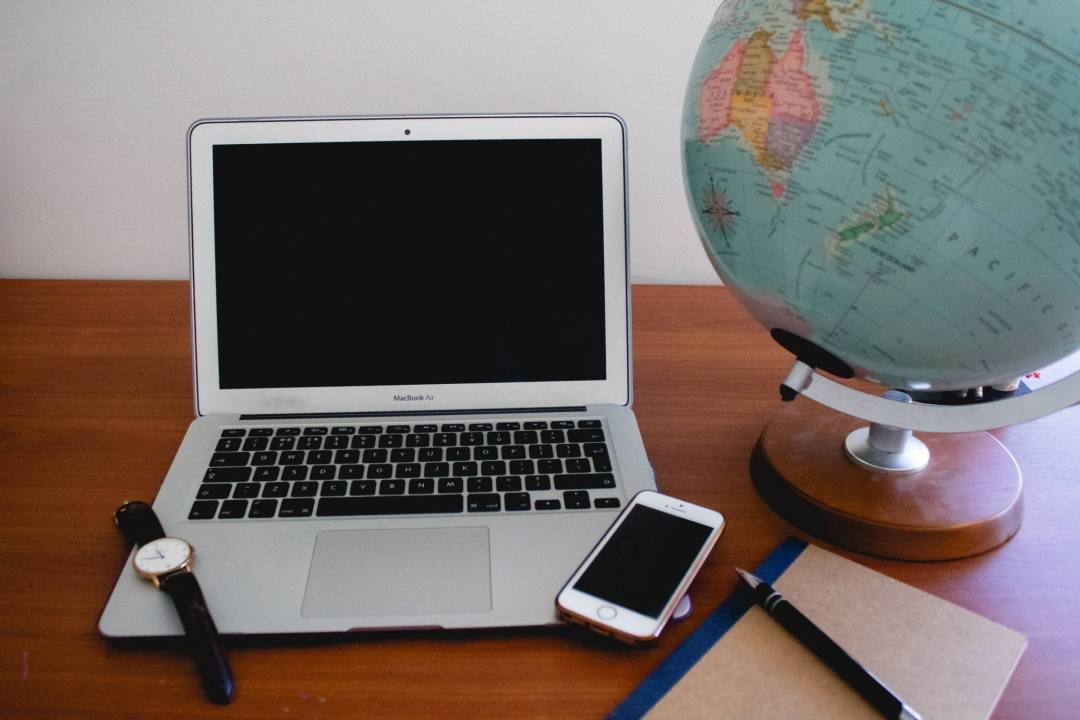office supplies and laptop on desk with globe