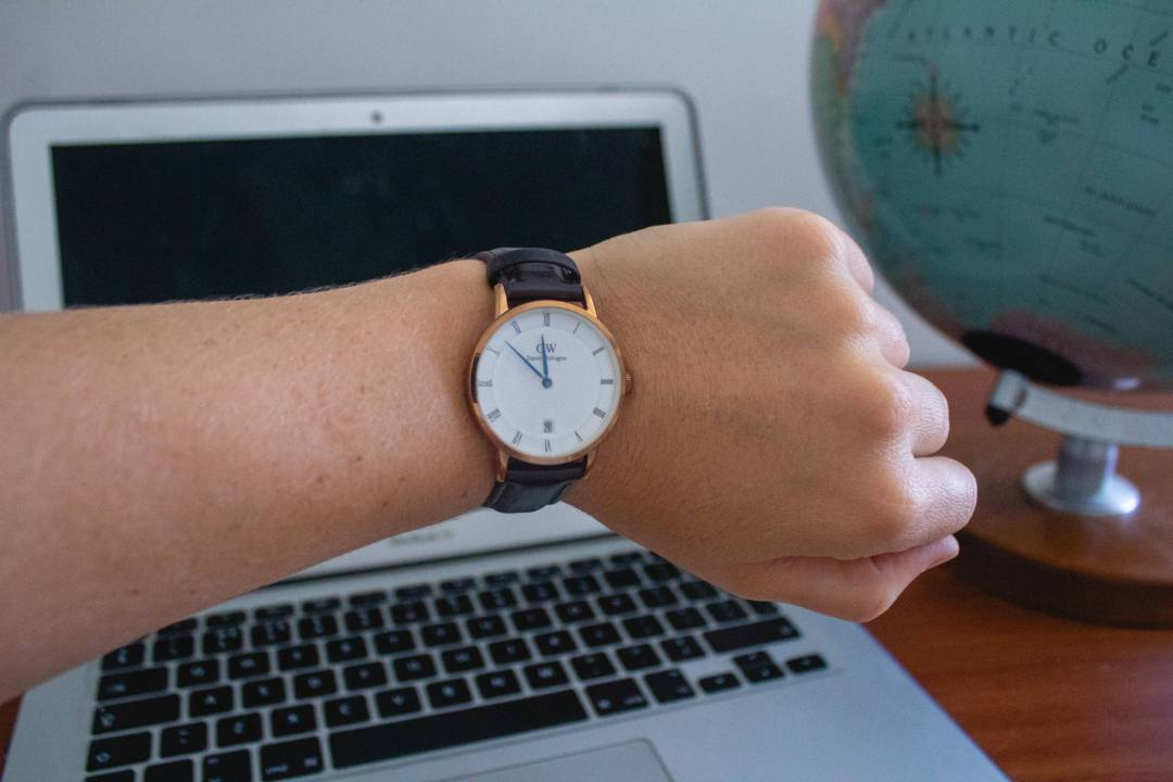 wristwatch in front of laptop and globe
