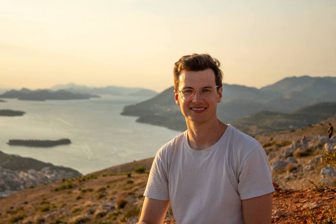 man smiles in front of sunset from mount srd summit
