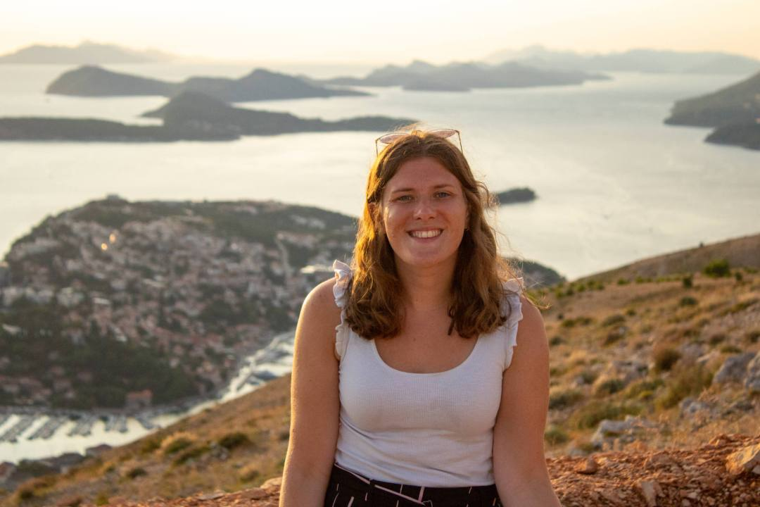 woman smiles in front of view over dubrovnik from mount srd