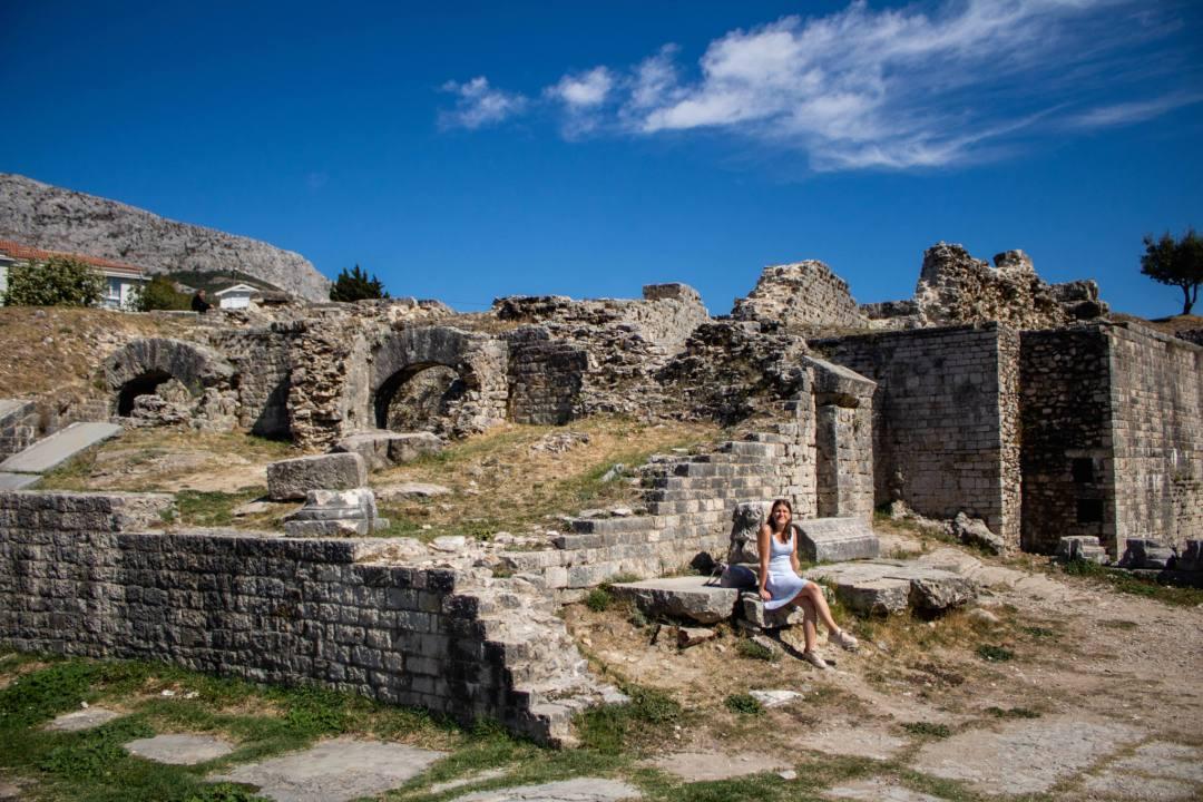 woman sits by roman amphitheatre ruins