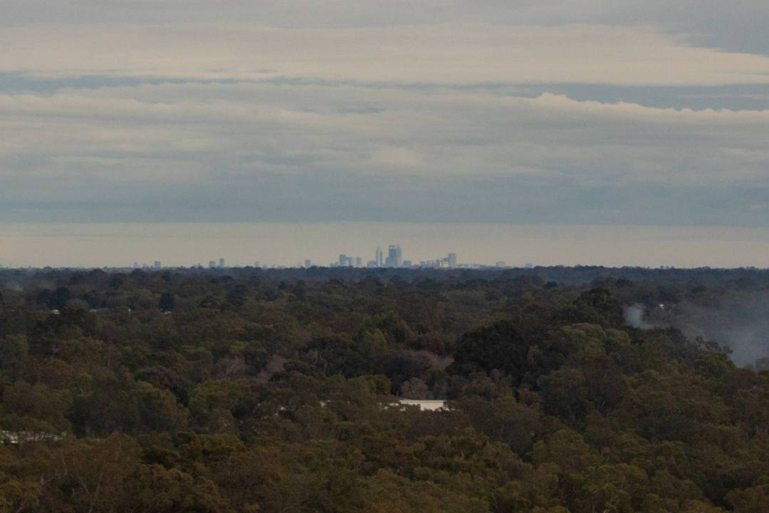 view over treetops and smoke to see faint outline of perth city