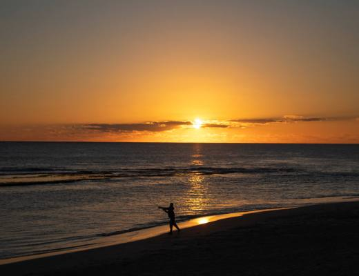 man throws fishing line into ocean at sunset over Yanchep