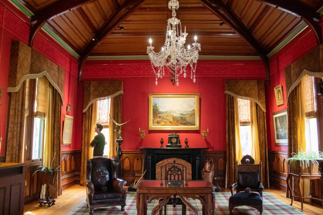 inside a living room with period furniture and decor inside Larnach Castle