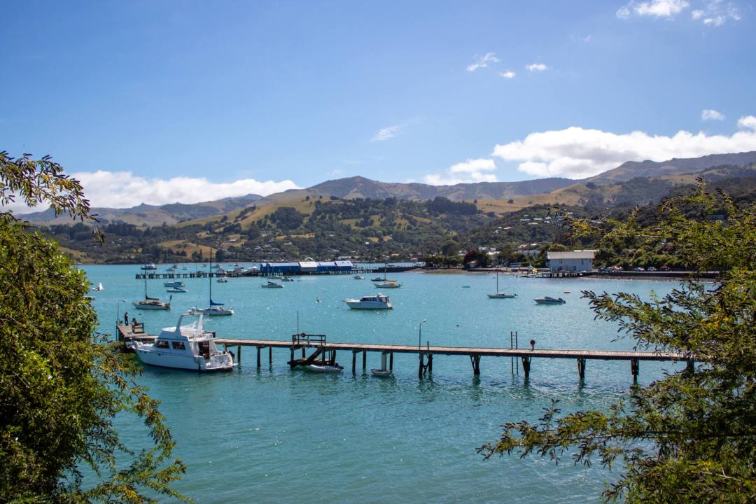 View over Akaroa Harbour with a long jetty leading to small boats