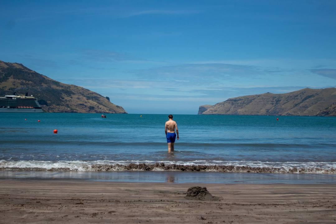 Man walks towards the sea at Wainui Beach